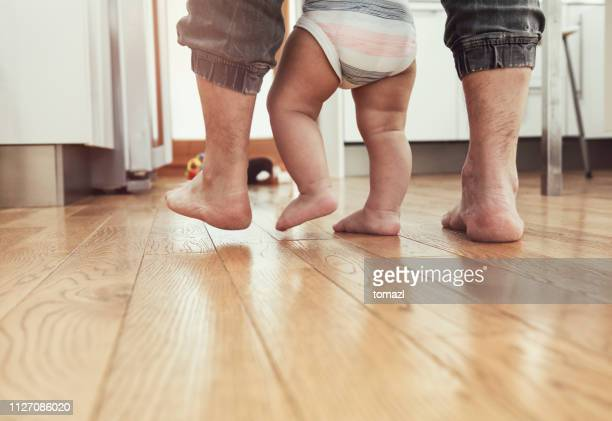 father teaching baby to walk - rear view - rite of passage stock pictures, royalty-free photos & images
