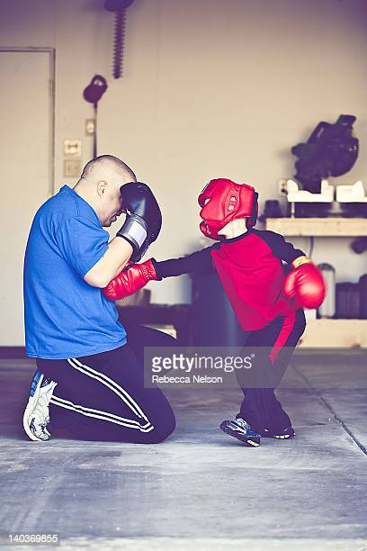 Father teaching boy how to box