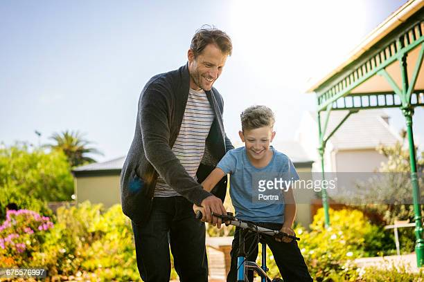 Father teaching boy to ride bicycle in yard