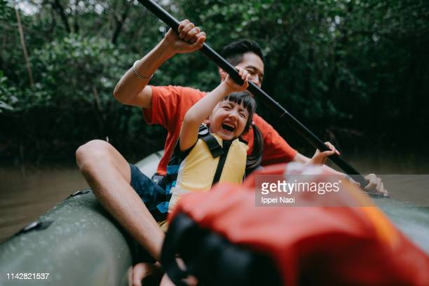 father teaching child how to paddle kayak in mangrove swamp, japan - buitensport stockfoto's en -beelden