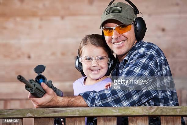 Father teaching child to handle gun