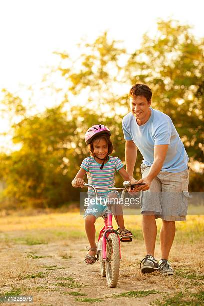 Father Teaching Child to ride a bicycle.