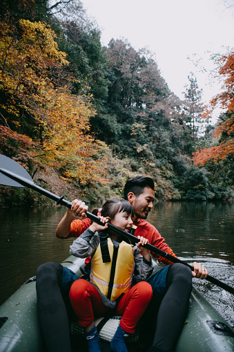 Father teaching daughter how to paddle kayak on river, Japan - gettyimageskorea