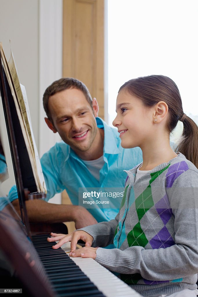 Father teaching daughter how to play the piano : Photo