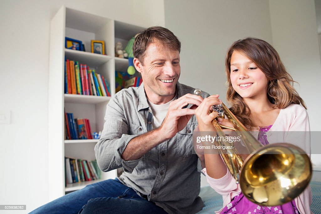 Father teaching daughter (8-9) how to play trumpet : Stock Photo