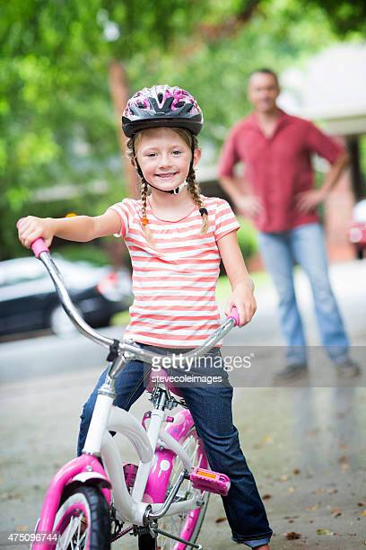 Father teaching daughter how to ride a bike.
