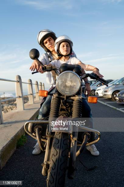 father teaching daughter motorcycle front brakes and handlebars - first occurrence stock-fotos und bilder