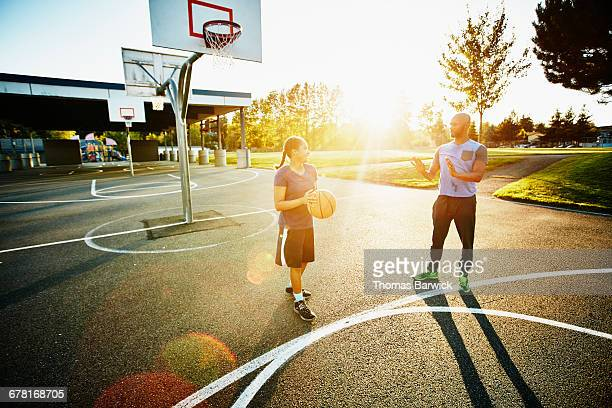 Father teaching daughter on basketball court
