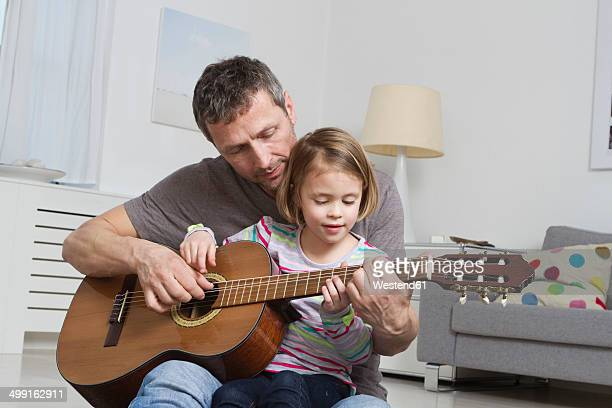 father teaching daughter to play guitar - gitarre stock-fotos und bilder