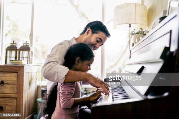 father teaching daughter to play piano - musical instrument stock pictures, royalty-free photos & images