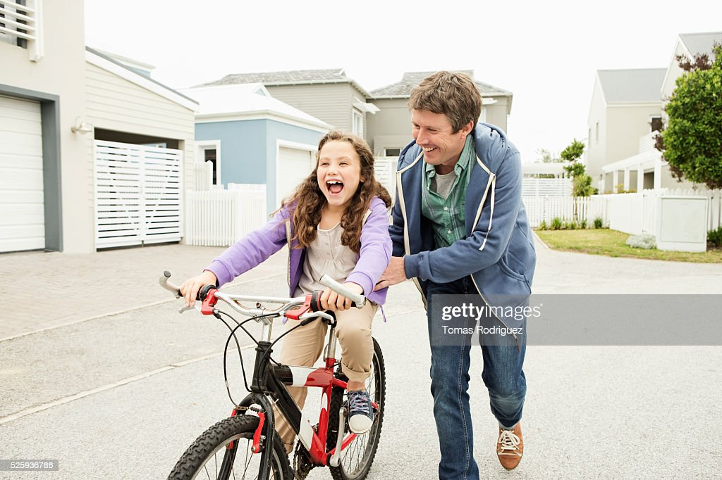 Father teaching daughter (6-7) to ride bicycle : Stock Photo