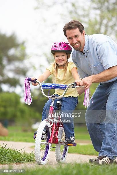 father teaching daughter (4-6) to ride bicycle, portrait - tassel stock pictures, royalty-free photos & images