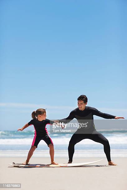 Father teaching daughter to surf on beach