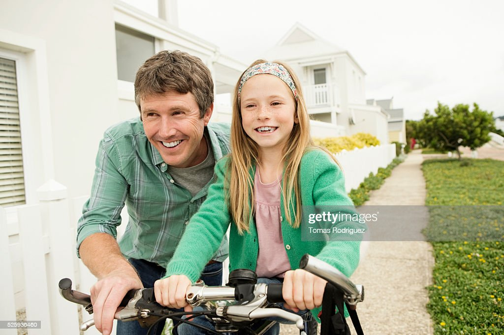 Father teaching girl (8-9) riding bicycle : Stock-Foto