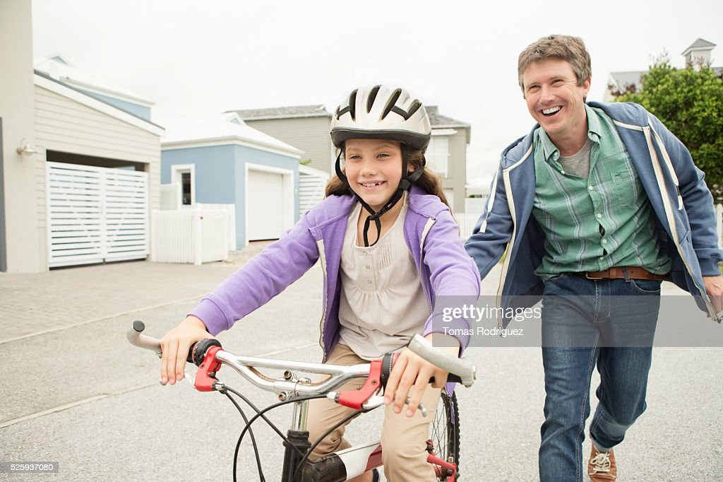 Father teaching girl (8-9) riding bicycle : ストックフォト