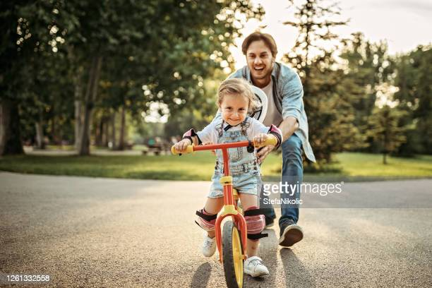 father teaching his daughter how to drive a bicycle - riding stock pictures, royalty-free photos & images