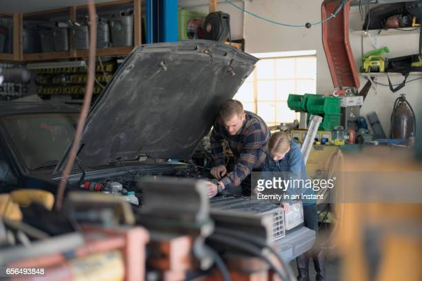 Father teaching his daughter how to fix a car engine