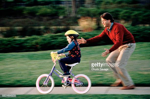 Father teaching his daughter how to ride a bicycle