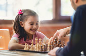 Father Teaching His Daughter to Play Chess At Home