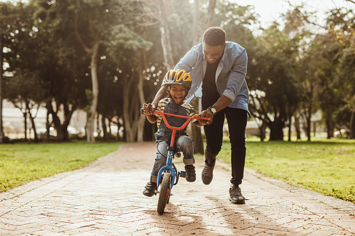 Father teaching his son cycling at park 1126785367