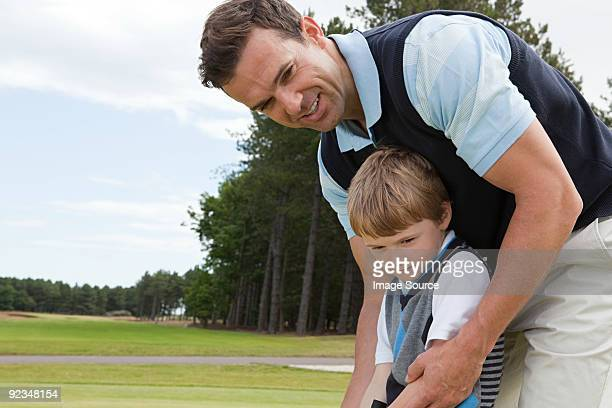 Father teaching his son golf