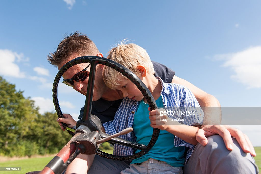 Father teaching his son to drive a tractor : Stock Photo