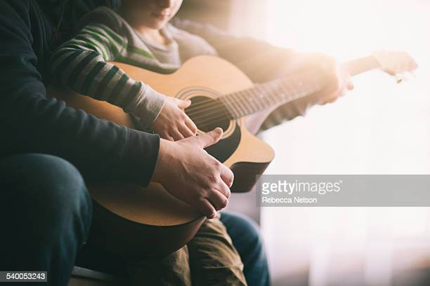 father teaching his son to play guitar - gitarre stock-fotos und bilder