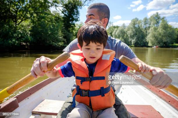 A father teaching his son to row a boat