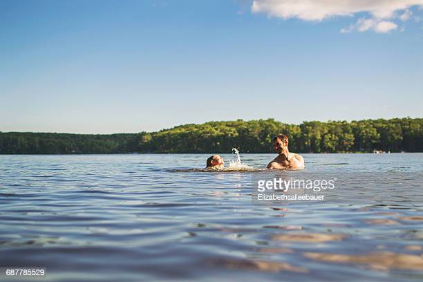 Father teaching his son to swim in a lake