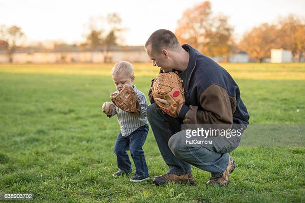 Father teaching his toddler son baseball in a park