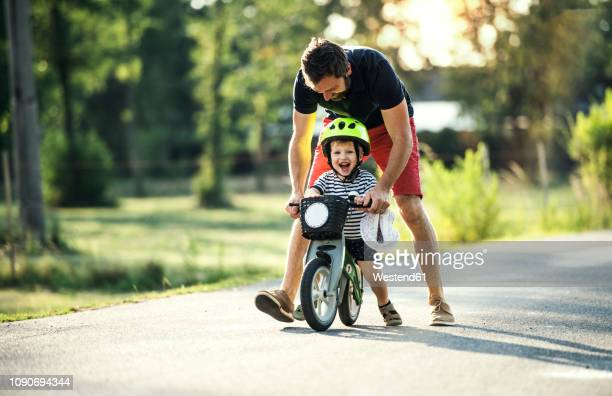father teaching little son riding bicycle - 乗る ストックフォトと画像