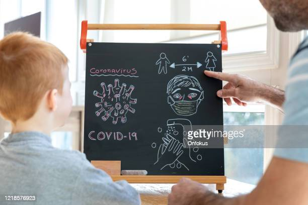 father teaching redhead son about coronavirus and covid-19 - showing respect stock pictures, royalty-free photos & images