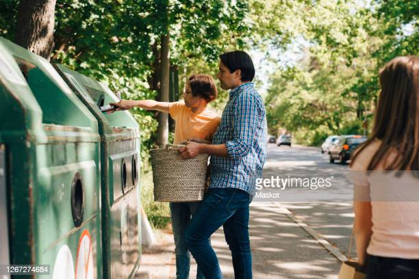 father teaching son about waste management during summer - rubbish bin stock pictures, royalty-free photos & images