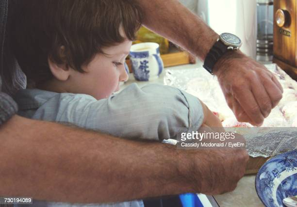 Father Teaching Son Food Preparation At Kitchen