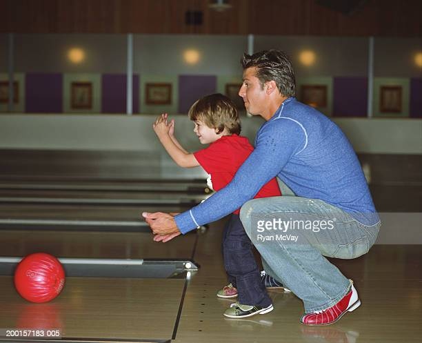 Father teaching son (2-4) how to bowl, side view