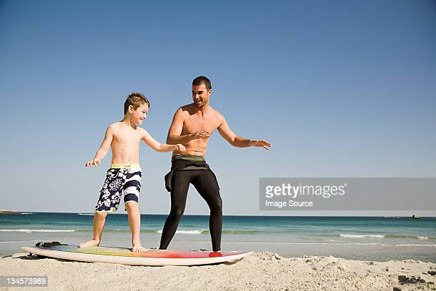 father teaching son how to surf - match sport stockfoto's en -beelden