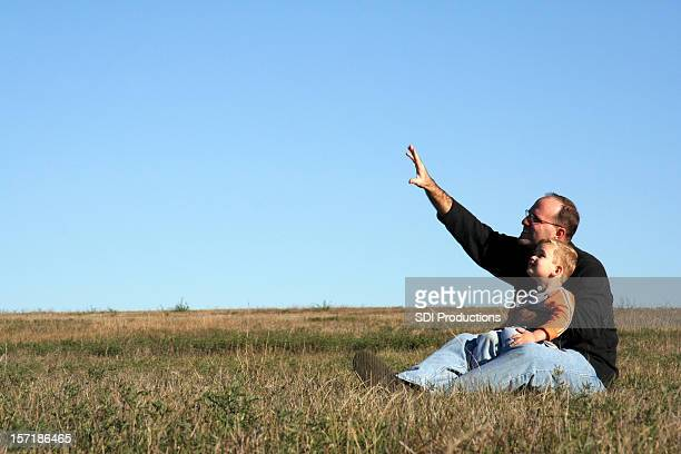 Father Teaching Son in Open Field, with Copy Space