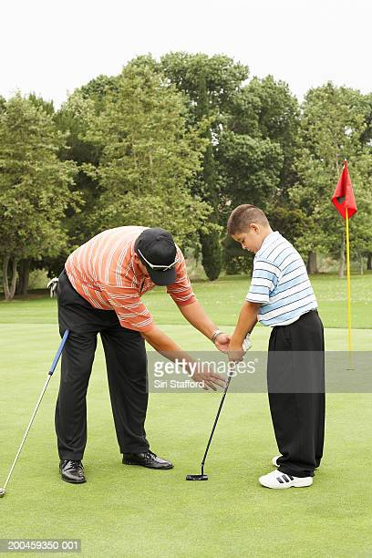 Father teaching son (8-10) proper way to hold putter