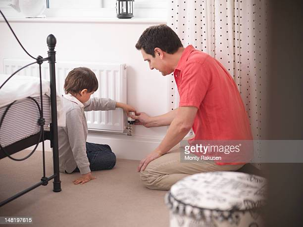 father teaching son to adjust thermostat on radiator in bedroom of energy efficient house - radiator heater stock photos and pictures