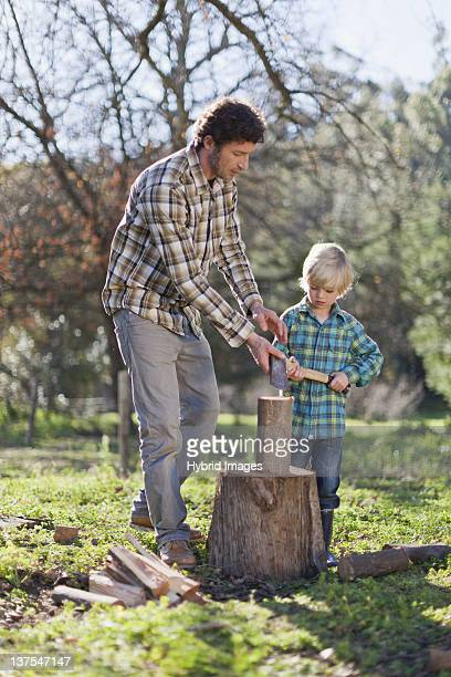 Father teaching son to chop wood