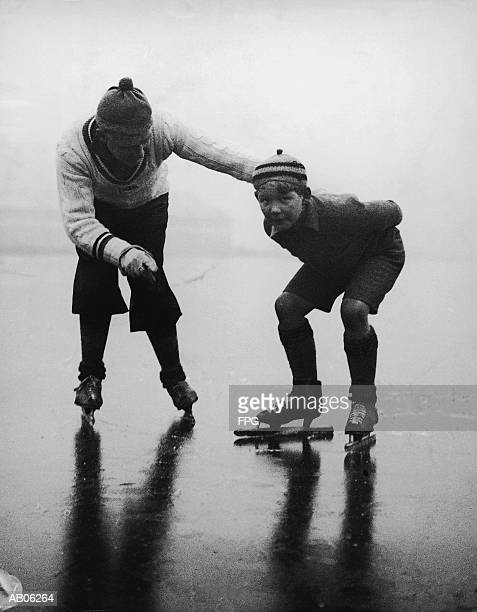 Father teaching son (10-12) to ice skate on frozen lake (B&W)