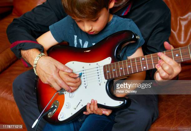 father teaching son to play the guitar - entertainment occupation stock pictures, royalty-free photos & images
