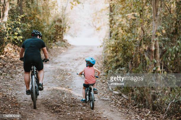 vader die zoon onderwijst om een fiets te berijden - alleenstaande vader stockfoto's en -beelden