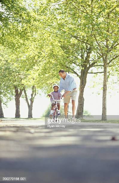 Father teaching son (4-5) to ride bicycle in park
