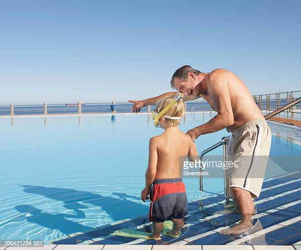 Father teaching son (6-8) to snorkel in outdoor pool, rear view of boy