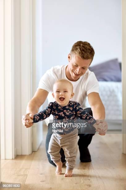 filho de pai ensinar a andar no corredor em casa - primeiros passos - fotografias e filmes do acervo