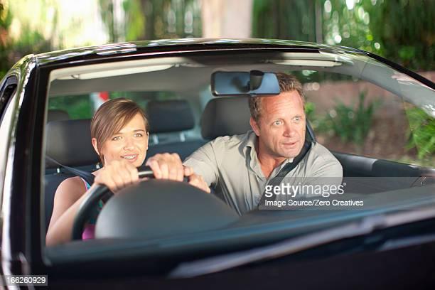 father teaching teenage daughter driving - indicare la via foto e immagini stock