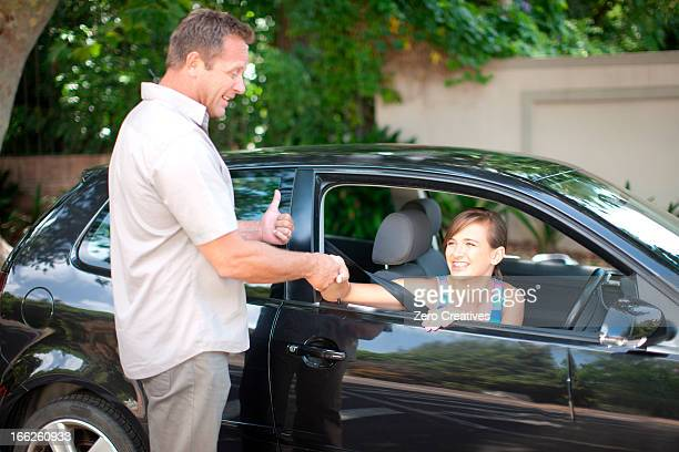 Father teaching teenage daughter driving