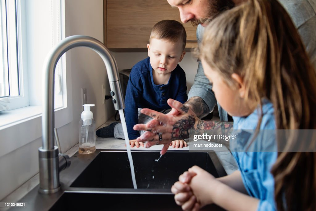 Father teaching young children how to wash their hands in quarantine isolation Covid-19 : Stock Photo