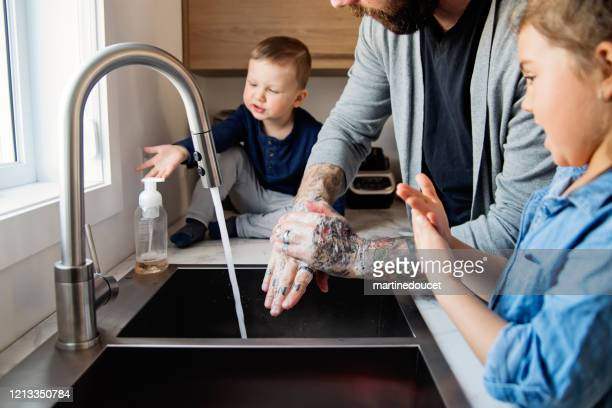 "father teaching young children how to wash their hands in quarantine isolation covid-19 - ""martine doucet"" or martinedoucet stock pictures, royalty-free photos & images"